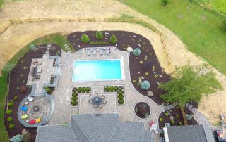 aerial view of home with inground pool, landscaping & paver patio