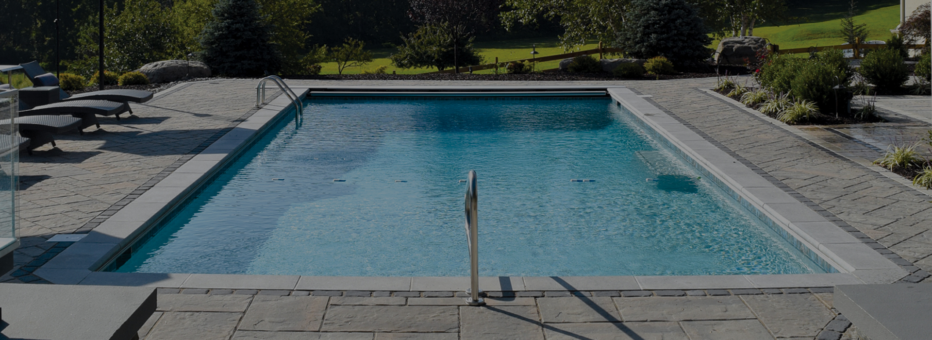 inground swimming pool with paver patio